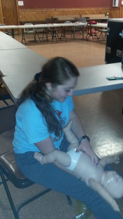 Kara performs compressions on a choking infant.